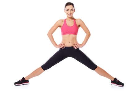 beine spreizen: Schöne junge Athlet posiert mit ihren weit gespreizten Beinen, und ihre Hände in die Hüften, als sie in die Kamera lächelt