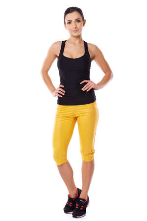 hands on hips: Attractive fit female athlete in sportswear posing with her hands on her hips, full body studio portrait on white