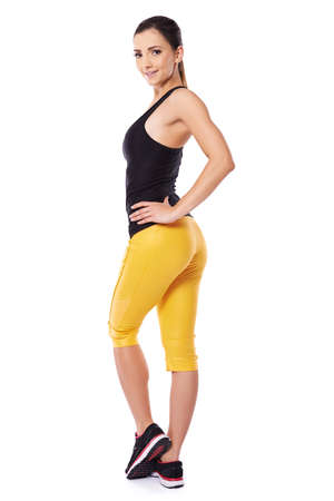 alluring: Sexy young woman in sportswear with a beautiful body and cute bum posing looking back over her shoulder at the camera Stock Photo