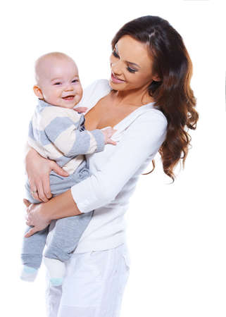 beaming: Beautiful young mother with a happy baby who is beaming at the camera clasped in her arms isolated on white Stock Photo