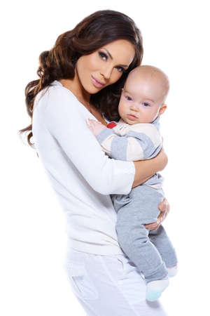 Beautiful loving mother holding her adorable little baby clasped in her arms standing sideways looking at the camera isolated on white
