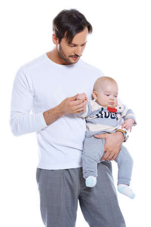 paternal: Loving father standing holding his small baby on his arm studio portrait isolated on white Stock Photo
