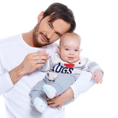 Proud young father posing with his baby cradled on his arm, both smiling happily at the camera isolated on white photo