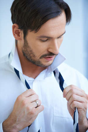 evening out: Attractive bearded young man putting on his tie evening out the lengths before tying the knot