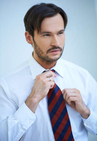 Attractive man straightening his tie looking carefully in the mirror as he prepares for work photo