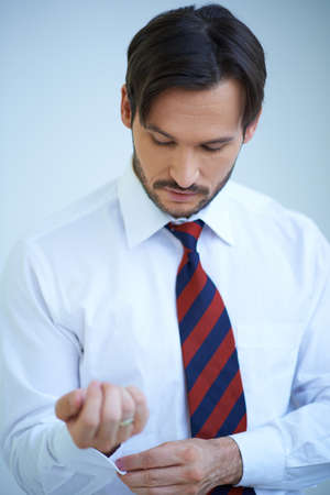 shirtsleeves: Attractive young man looking down at his arm doing up his shirt cuffs as he dresses ready for a day at the office Stock Photo