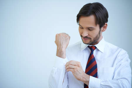 shirtsleeves: Young man buttoning his cuffs on his shirt as he gets dressed ready for a day at the office