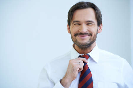 fastens: Happy bearded man grinning at the camera as he stands straightening his tie Stock Photo