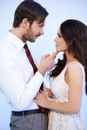 caresses: Romantic attractive couple standing close together facing one another staring into each others eyes as the man caresses her chin with his finger
