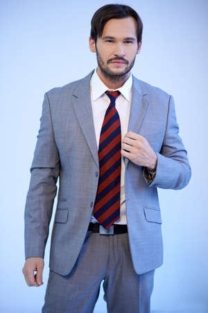 Handsome bearded young businessman standing in a grey suit with the jacket unbuttoned looking at the camera, three quarter studio portrait on grey Stock Photo - 17221047