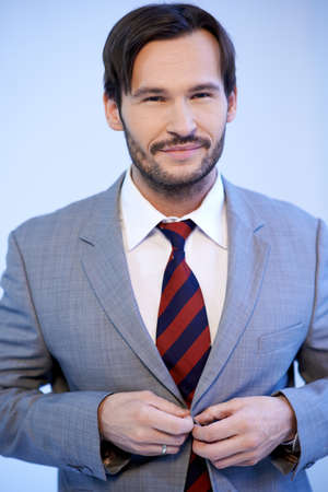 Smiling good looking young businessman standing buttoning his jacket, upper body studio portrait on grey Stock Photo - 17221041