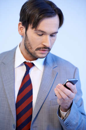 Unimpressed business man reading a text message on his mobile phone, studio upper body cropped portrait photo