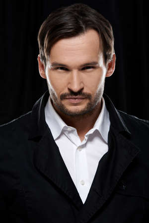 suave: Suave handsome bearded young man in a white shirt and black jacket , head and shoulders studio portrait on a dark background