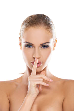 Beautiful woman with bare shoulders making a shushing gesture holding her index finger to her lips as she asks for silence or secrecy for a surprise, studio portrait isolated on white Stock Photo