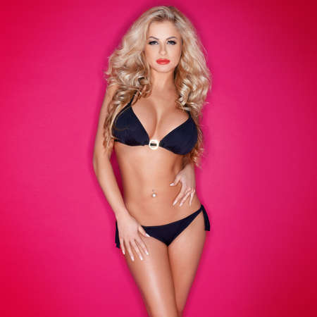 Glamorous busty blonde model with lovely long curly hair and a gorgeous figure posing in a black bikini on a hot pink studio background with vignetting Stock Photo