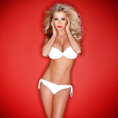 mujer rubia desnuda: Hermosa modelo sexy rubia hermosa con el pelo ondulado largo y un cuerpo escultural posando en lencer�a blanca sobre un fondo rojo con vi�etas estudio