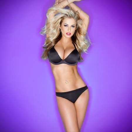 Beautiful sexy blonde woman with large breasts posing with her arms raised above her head in black lingerie against a purple studio background with vignetting