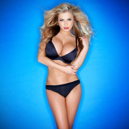 Glamorous femme sinueuse blonde avec un corps sexy et gros seins pose en lingerie noire sur un fond de studio bleu avec vignettage