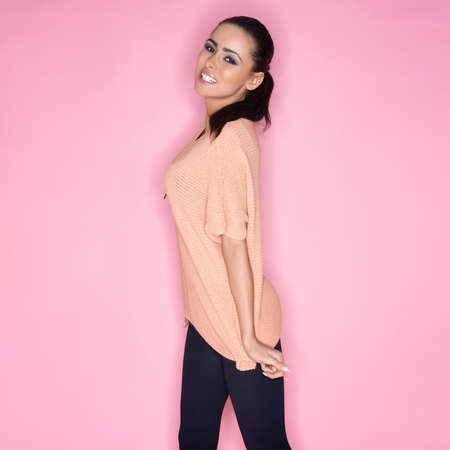 busty woman: Happy carefree beautiful woman with a busty figure in trendy casual clothes smiling happily at the camera on a pink studio background