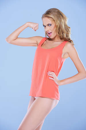 flex: Spoof image of a beautiful slender blonde woman in a skimpy miniskirt flexing her rather underdeveloped arm muscles with a look of determination Stock Photo