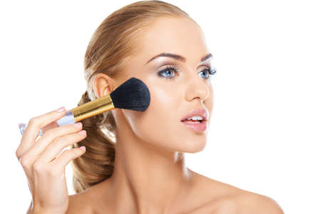 Beautiful blonde woman applying blusher or foundation powder to her cheek with a large soft cosmetics brush, beauty portrait isolated on white photo