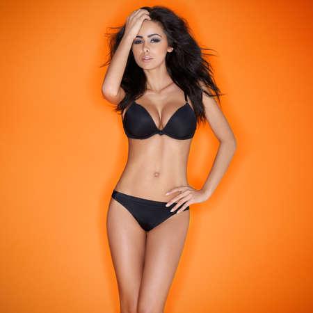 Hot femme sensuelle jeune femme brune posant en lingerie noire sexy Banque d'images