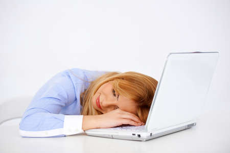 Beautiful young blonde woman daydreaming smiling with her head on the laptop at her desk Stock Photo - 17357710