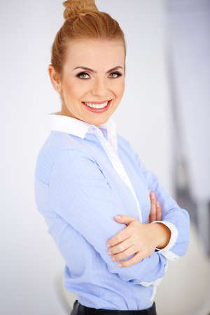 dress code: Portrait of a pretty blonde girl with arms crossed and smiling. White background Stock Photo
