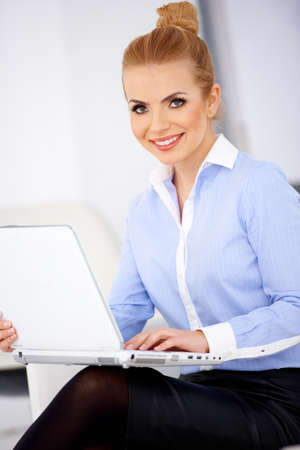 Pretty blond girl and laptop, sitting and smiling photo
