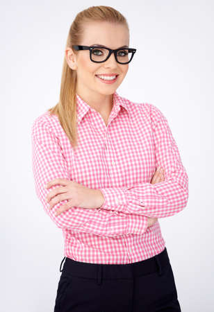 dress code: Portrait of a happy blonde geek girl in pink shirt and glasses Stock Photo