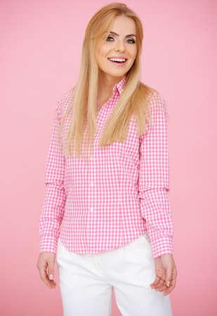 Blond girl having fun posing in a pink blouse Stock Photo - 17541012