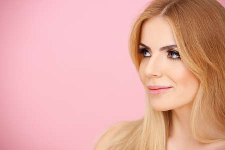 Pretty blond girl over pink in profile with copyspace Stock Photo - 17541011