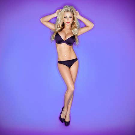 Femme Blonde En Bikini Avec La Main Sur La Tête Isolé Sur Fond Bleu