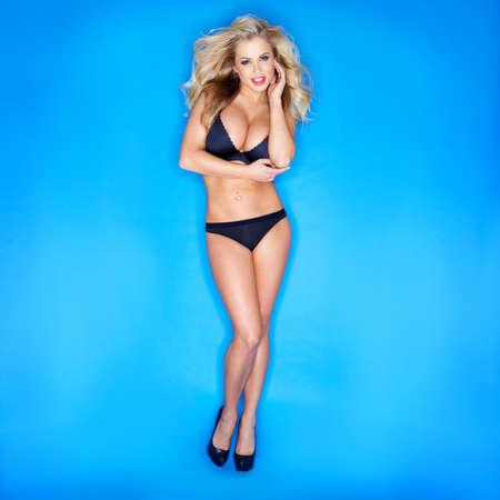 Blonde Woman In Bikini isolé sur fond bleu Banque d'images