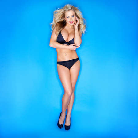 Blonde Woman In Bikini Isolated Against Blue Background photo
