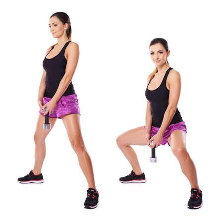 legs spread: Atletica giovane donna che lavora con manubri mostrato in due posizioni in piedi lateralmente alla macchina fotografica con le gambe divaricate in piedi e flettendo le ginocchia con i bilancieri di fronte a lei
