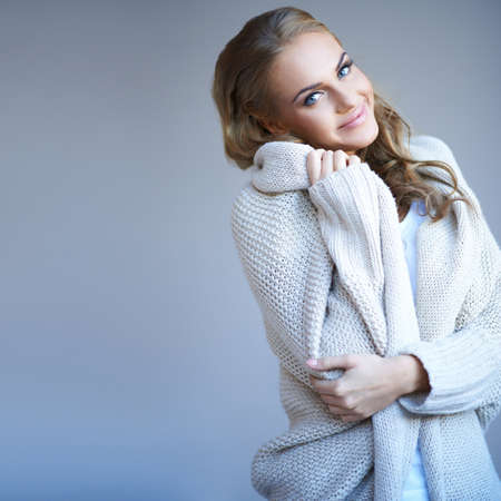 winter woman: Beautiful woman in winter fashion snuggling up in the warmth of her stylish knitted wool jersey with a smile of pleasure Stock Photo