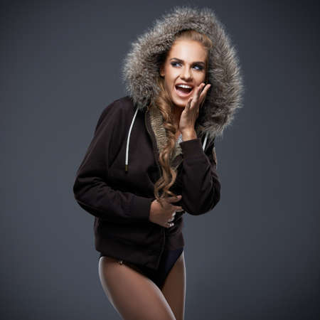 tantalising: Beautiful woman in a winter jacket with a fur trimmed hood posing with bare legs against a grey studio background