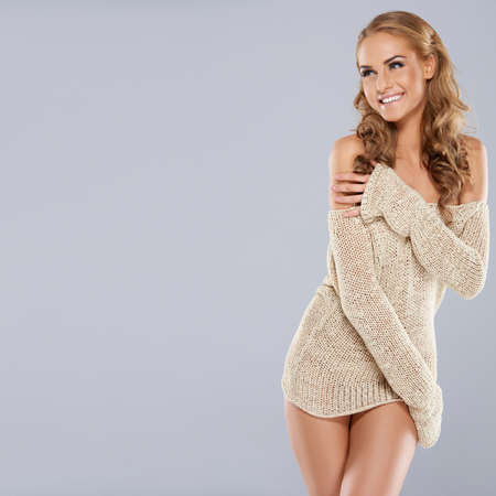 vivacious: Playful beautiful blonde model laughing as she wraps her arms around the skimpy trendy off the shoulder top that she is wearing