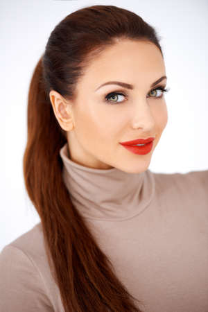 ponytail: Head and shoulders portrait of a beautiful elegant woman with neatly tied long brunette hair and sexy red lipstick isolated on white