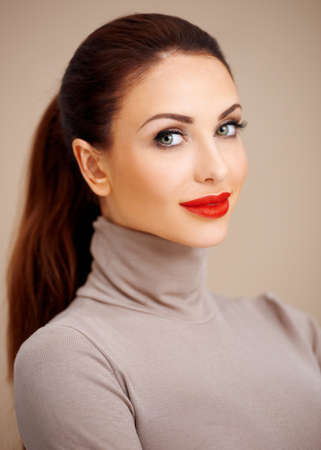 hair tied: Beautiful glamorous young woman in a stylish polo neck with vivid red lipstick and her long brunette hair tied back neatly in a ponytail on a beige studio background