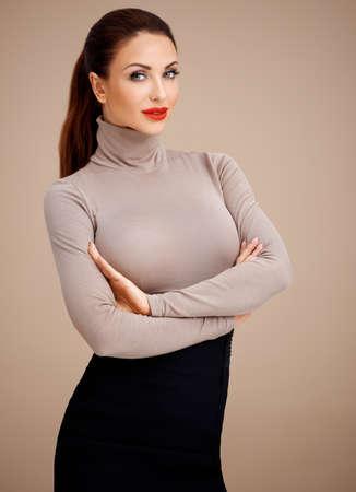 busty: Mooie welgevormde glamoureuze professionele vrouw met haar haar vastgebonden keurig terug met haar armen gevouwen kijken naar de camera op een beige achtergrond