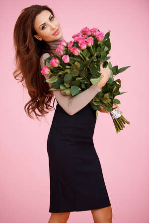Beautiful sexy woman standing sideways looking at the camera clasping a large bouquet of Valentine roses