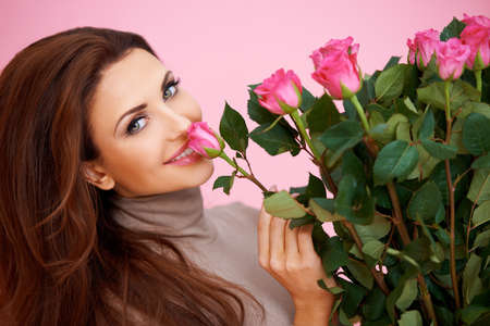 Beautiful woman with a large bouquet of flowers in her arms smelling a fragrant pink rose Stockfoto