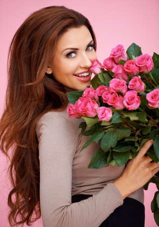 Laughing romantic sexy woman with long brunette hair holding a large bouquet of pink roses for her anniversary or Valentines photo