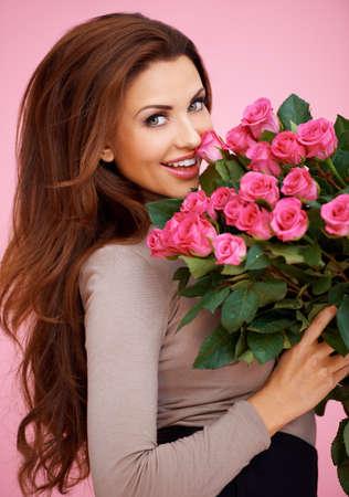 Rire femme romantique sexy avec des cheveux brune longue tenue un gros bouquet de roses roses pour son anniversaire ou Valentines