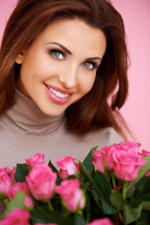 Gorgeous brunette woman with beautiful big eyes holding a bunch of romantic pink roses Foto de archivo