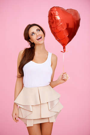 sexy brunette: Vivacious brunette woman ina sexy miniskirt with a red heart shaped Valentine balloon in her hand on a pink studio background