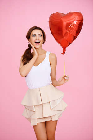 Laughing playful woman with a red heart shaped balloon celebrating her anniversary or Valentines Day on a pink studio background