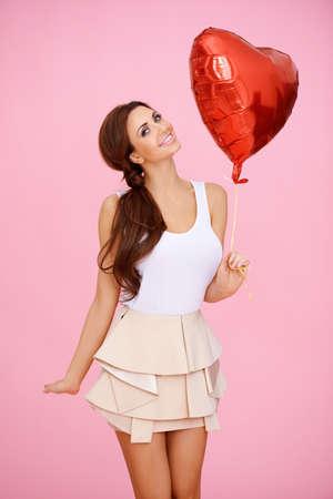 Vivacious femme sexy avec un ballon rouge de coeur pour les fêtes de la Journée parti lui-Valentin, mariage, fiançailles ou d'anniversaire